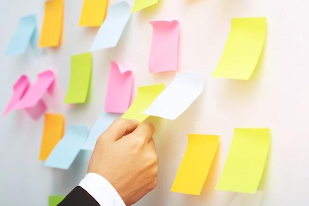 Feche a mão de pessoas de negócios, cole notas na parede da sala de reuniões
