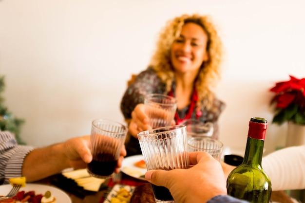 Feche a mão de um homem segurando uma taça com vinho e tilintando com outras três pessoas à mesa comendo - jantar em família juntos se divertindo