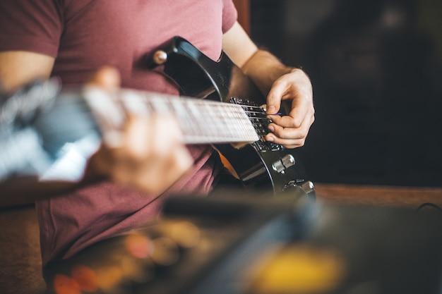Feche a mão de um jovem tocando uma guitarra elétrica profissional preta, instrumento musical, entretenimento