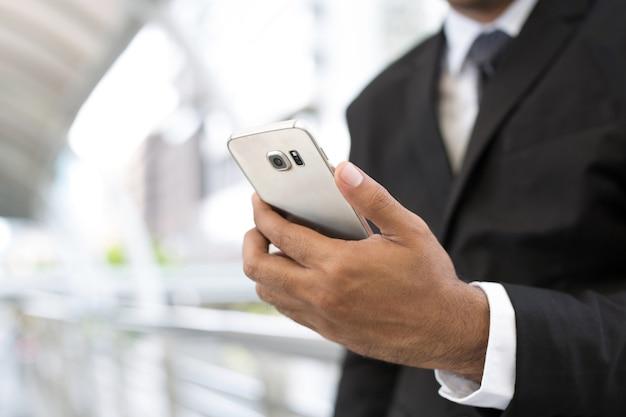 Feche a mão de um jovem usando um telefone móvel inteligente.