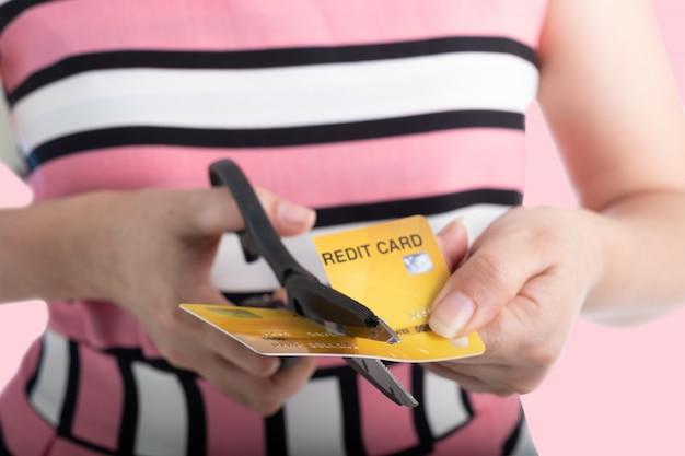 Feche a mão de uma jovem mulher cortando um cartão de crédito com uma tesoura para parar de gastar em compras no rosa