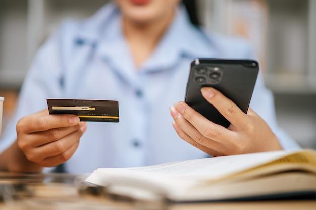 Feche a mão de uma jovem usando o celular, compras online e pagamento com cartão de crédito