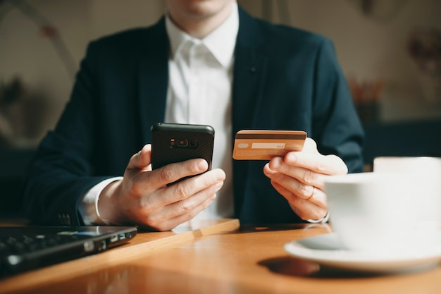 Feche a mão de uma mão masculina usando um cartão de crédito e um smartphone para transações online enquanto está sentado no café.