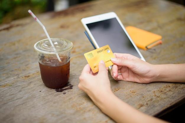 Feche a mão de uma mulher está segurando o cartão de crédito e usando o tablet na cafeteria