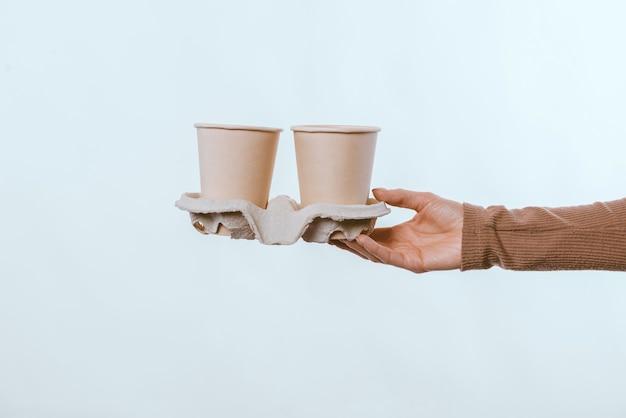 Feche a mão de uma mulher segurando duas xícaras de café para levar, sobre um fundo branco