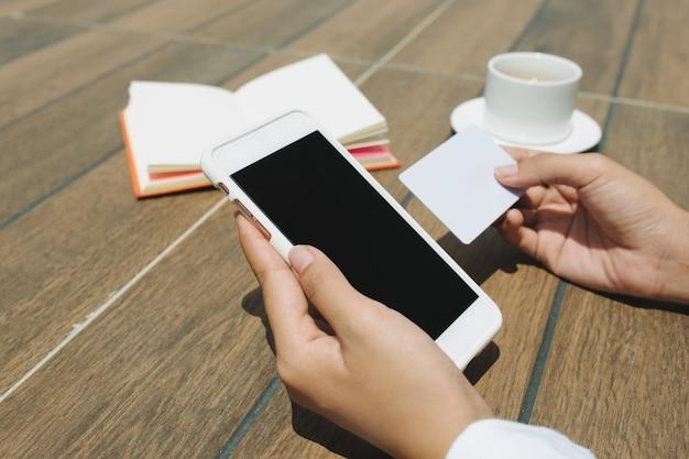 Feche a mão de uma mulher segurando um cartão de crédito e um celular de tela em branco sentado na cafeteria