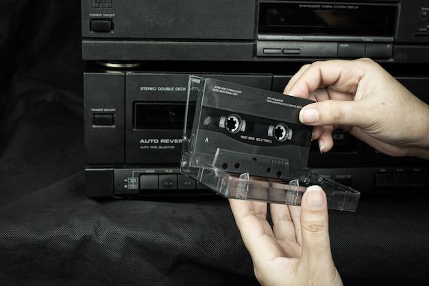 Feche a mão de uma mulher segurando um compacto de fita cassete em um antigo fundo de fita de áudio reproduzido