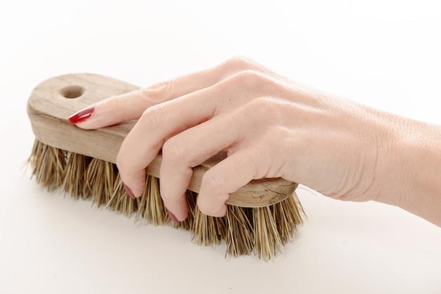Feche a mão de uma mulher usando a escova de limpeza