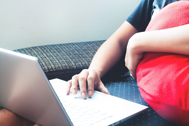 Feche a mão de uma mulher usando o laptop em casa. relaxamento ou conceito de tecnologia e estilo de vida