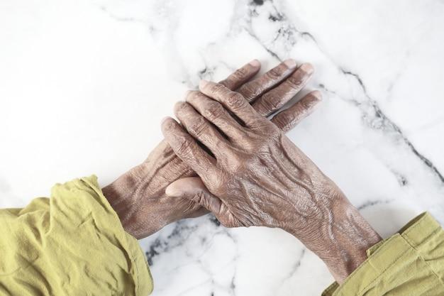 Feche a mão de uma pessoa idosa isolada no branco