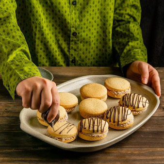 Feche a mão decorando biscoito com creme