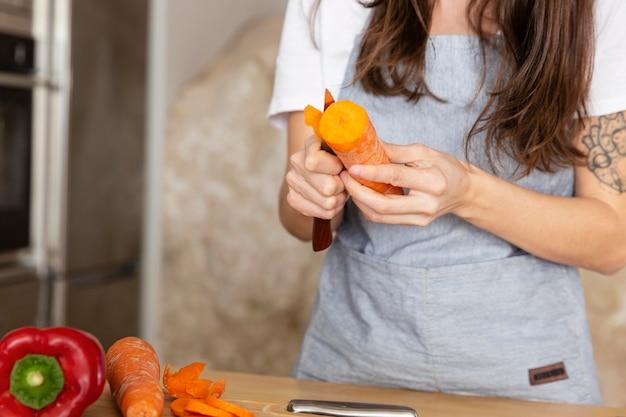 Feche a mão descascando cenoura