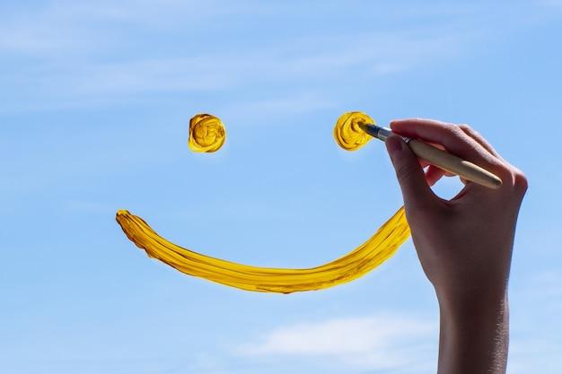 Feche a mão desenhando um rosto sorridente no vidro contra um céu azul