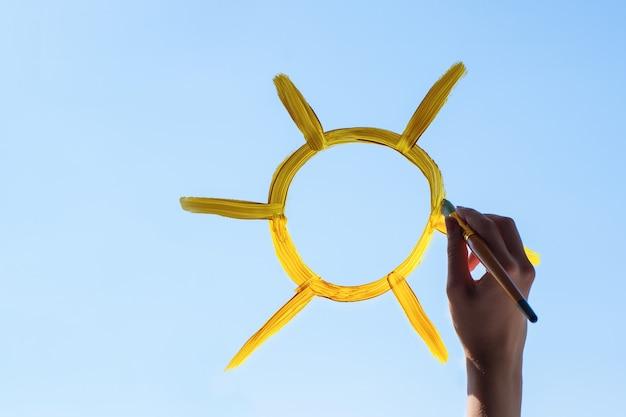 Feche a mão desenhando um sol amarelo no vidro contra um céu azul