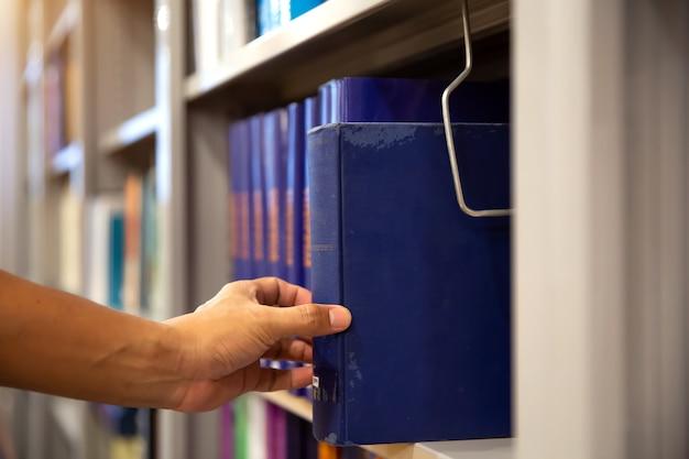 Feche a mão do aluno escolhendo livros das prateleiras da biblioteca