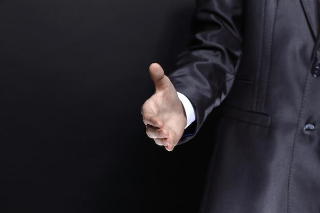 Feche a mão do empresário para um aperto de mão isolado em um fundo preto