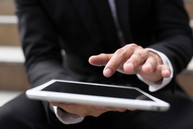 Feche a mão do empresário trabalhando usando um tablet digital Foto Premium