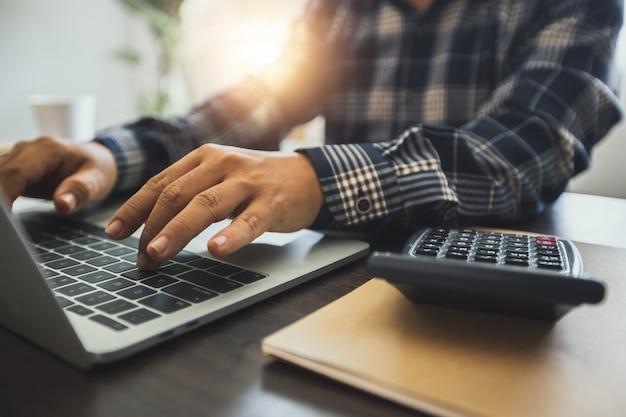 Feche a mão do empresário usando o número recorde e o orçamento financeiro no laptop