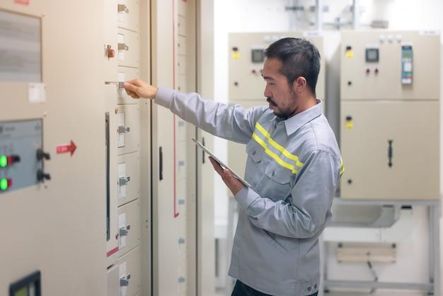 Feche a mão do engenheiro ou eletricista trabalhando para verificar o sistema elétrico com o tablet na fábrica.