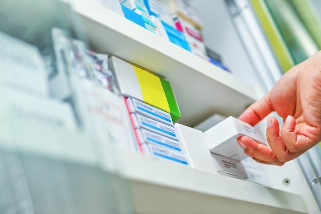 Feche a mão do farmacêutico segurando a caixa de remédios na drogaria da farmácia
