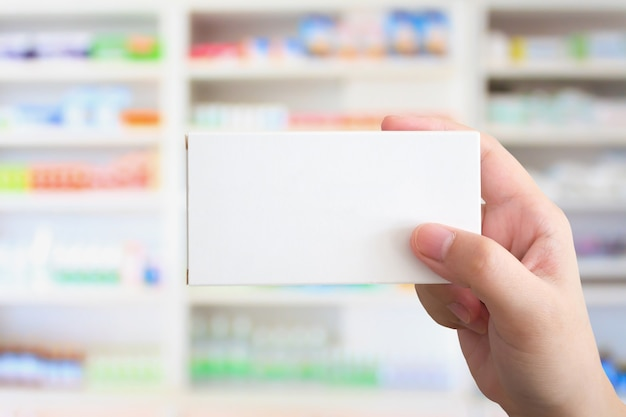 Feche a mão do farmacêutico, segure a embalagem da caixa de remédios com prateleiras de remédios na farmácia
