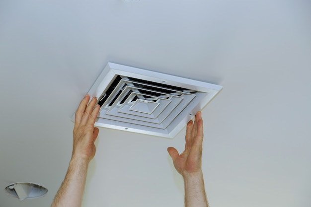 Feche a mão do homem a instalar a tampa de ventilação do teto