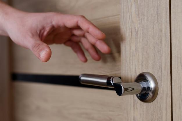 Feche a mão do homem alcançando a maçaneta da porta, abrindo a porta