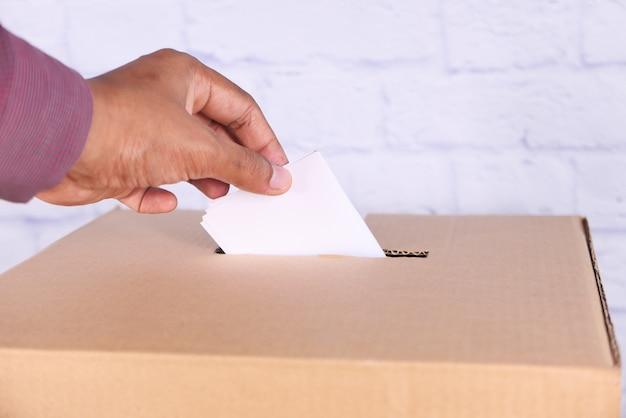 Feche a mão do homem colocando o cartão na caixa com slot,