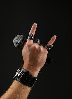 Feche a mão do homem com anéis de metal e pulseira mostrando sinal de pedra com chifres do diabo, segurando o microfone sobre fundo preto, vista lateral