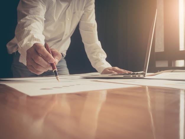 Feche a mão do homem de negócios, segurando a caneta apontando no gráfico de papel gráfico