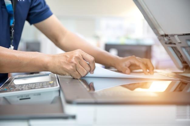 Feche a mão do homem do escritório usando a copiadora.