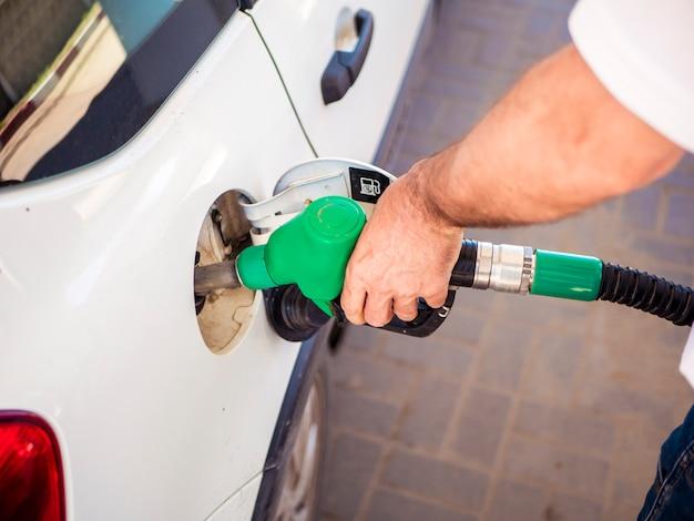Feche a mão do homem encher o carro branco com combustível