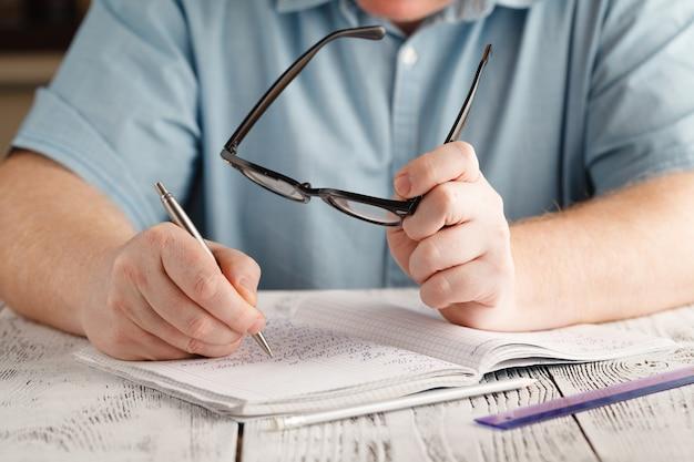 Feche a mão do homem escrevendo no papel, escrevendo matemática bagunçada, estudante segurar óculos, conceito de educação