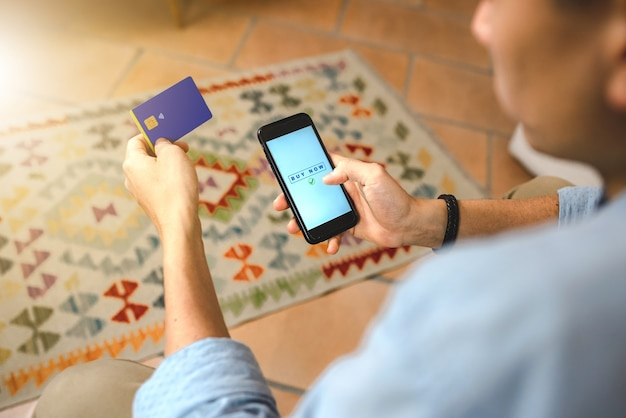 Feche a mão do homem fazendo compras online com o smartphone sentado no sofá. pagamento pela internet com cartão de crédito. conceito de home banking e tecnologia.
