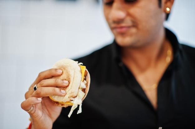 Feche a mão do homem indiano com hambúrguer delicioso.