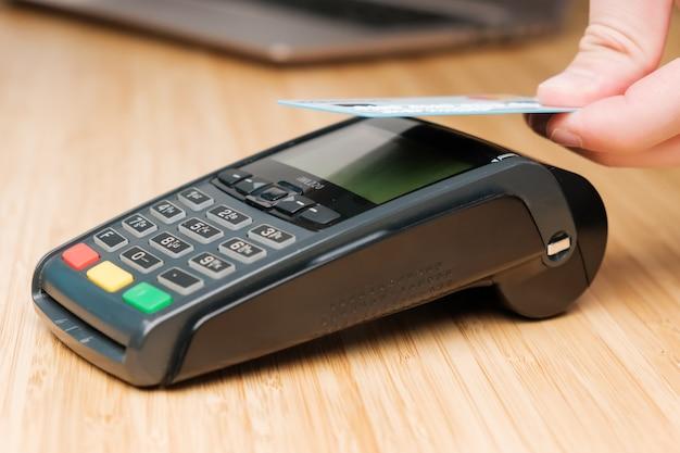 Feche a mão do homem pagando com cartão de crédito sem contato com tecnologia nfc usando pagamento sem fio