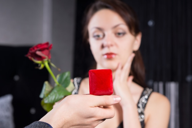 Feche a mão do homem segurando a caixa de presente de joias vermelhas para sua namorada.