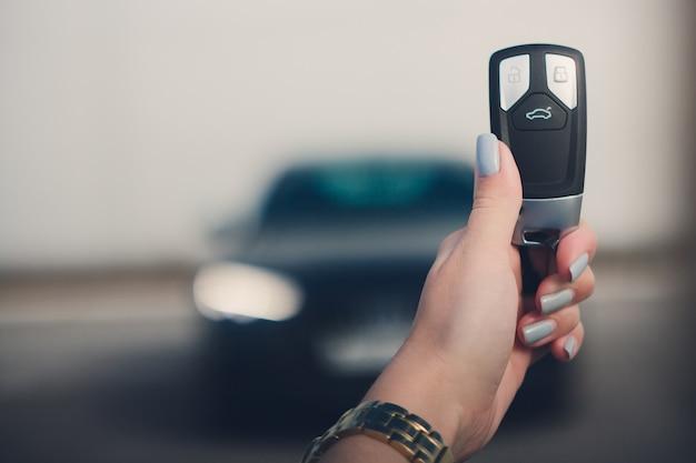 Feche a mão do homem segurando a chave do carro com o carro preto borrado no fundo.
