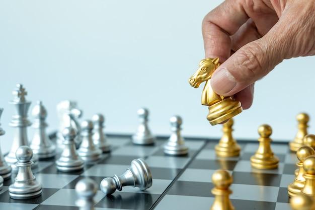Feche a mão do homem segurando o cavalo de xadrez de ouro no tabuleiro de xadrez, copie o espaço para o seu texto.