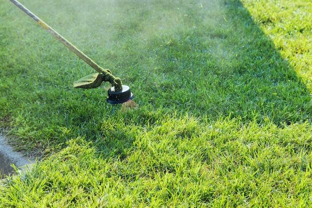 Feche a mão do homem usando o cortador de grama cortando grama no foco seletivo verde disponível