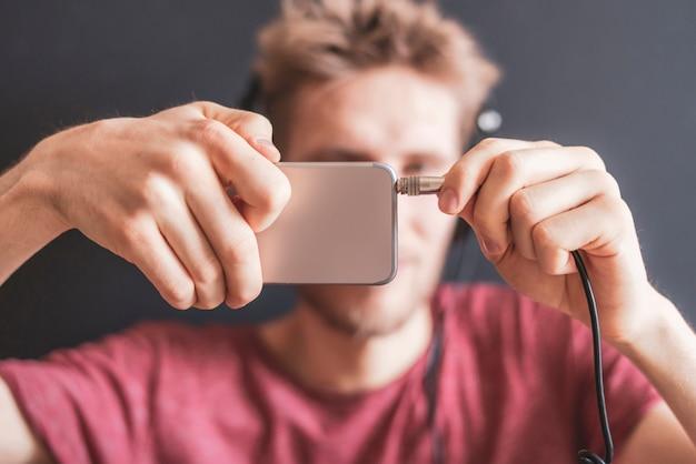 Feche a mão do jovem plugue o cabo do fone de ouvido no celular b
