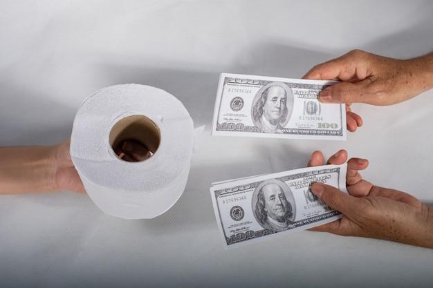 Feche a mão do lenço de papel de sellbuy segurando o lenço de papel higiênico e o dinheiro da nota de 100 dólares americanos