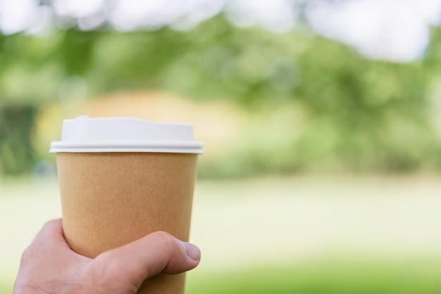 Feche a mão do macho segurando o copo de café.