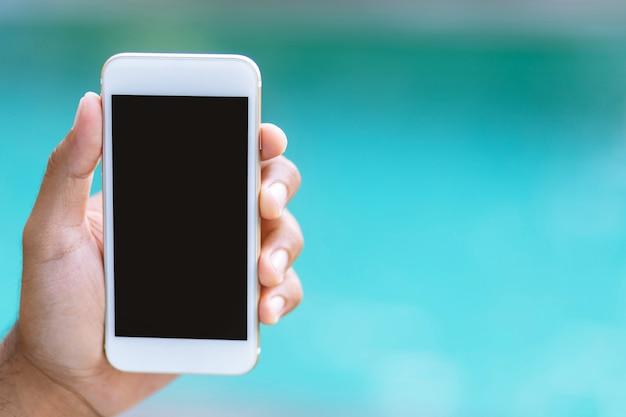 Feche a mão do macho segurando um telefone inteligente móvel branco com tela em branco vazia. espaço vazio para o texto. conceito de tecnologia e viagens de férias
