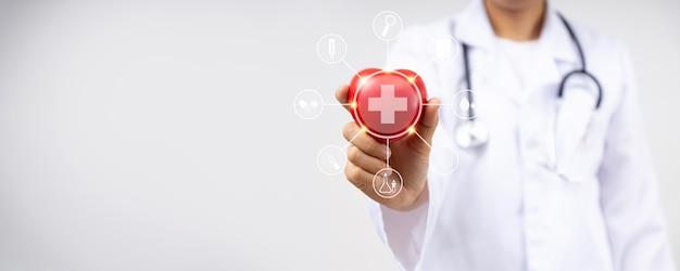 Feche a mão do médico segurando um coração vermelho para doença cardíaca para o conceito de serviço de seguro saúde