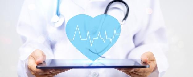 Feche a mão do médico segurando um tablet com coração azul para doenças cardíacas para o conceito de serviço de seguro de saúde