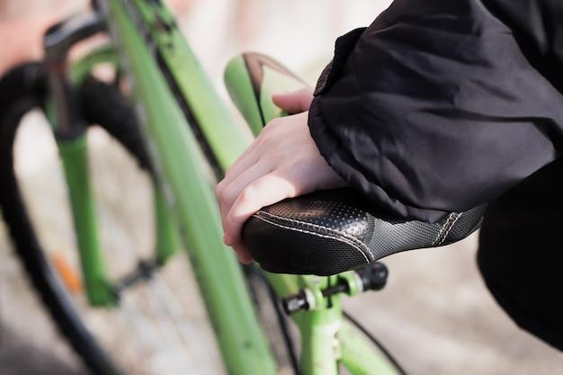 Feche a mão do menino no selim da bicicleta, tempo de primavera, feche o assento da bicicleta.