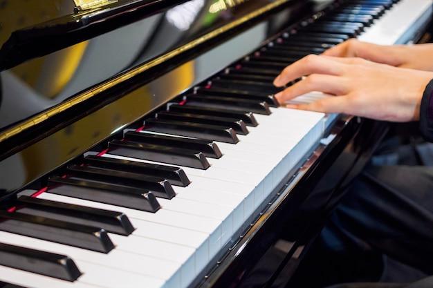 Feche a mão do músico tocando piano