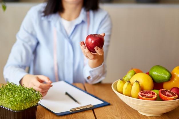 Feche a mão do nutricionista com vegetais e frutas