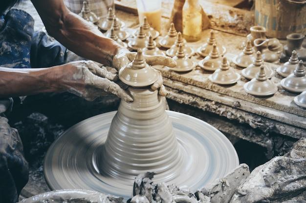 Feche a mão do oleiro profissional fazendo tampa de pote de estilo tailandês em uma roda de oleiro